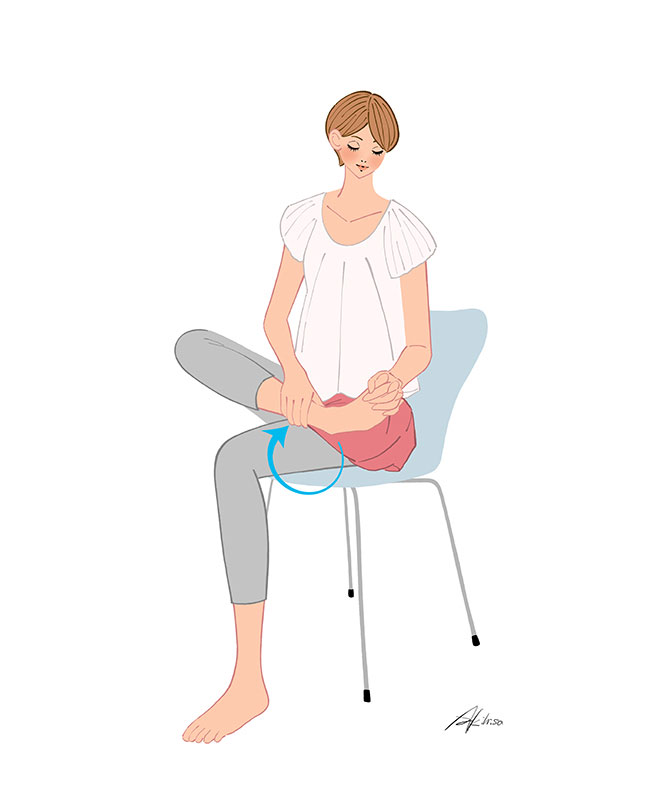 椅子に座り足首を回すストレッチをする女の子