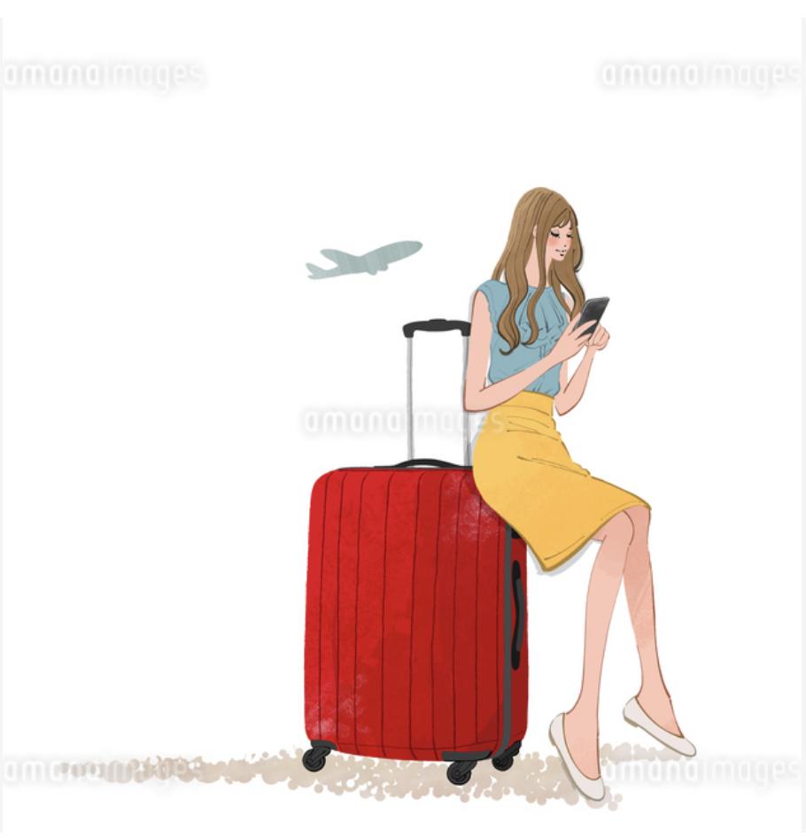 スーツケースに座りスマホを見る旅行に出かける女性